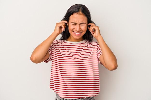 指で耳を覆っている白い背景で隔離された若いラテン女性は、大声で周囲によってストレスと絶望的です。