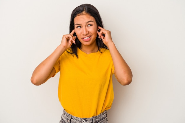 指で耳を覆う白い背景で隔離された若いラテン女性は、大声で周囲によってストレスと必死になりました。
