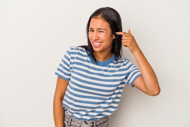 手で耳を覆う白い背景で隔離の若いラテン女性。