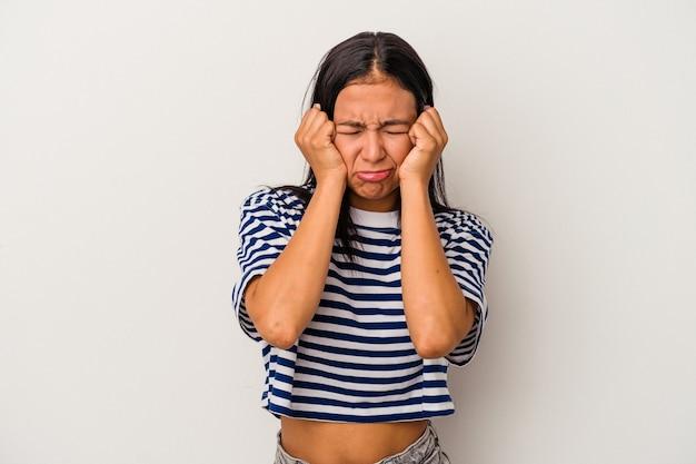 Молодая латинская женщина, изолированные на белом фоне плачет, недовольна чем-то, агонией и концепцией замешательства.