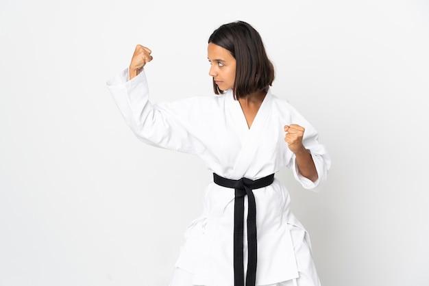 Молодая латинская женщина, изолированные на белом фоне, занимается карате