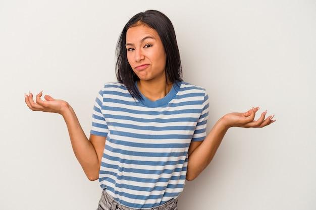 ジェスチャーを疑って肩をすくめる白い背景に孤立した若いラテン女性。