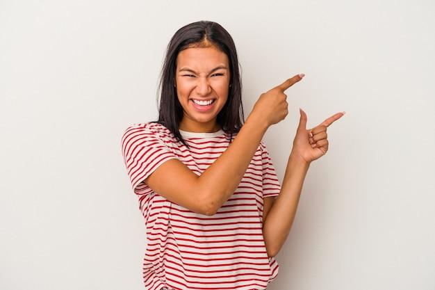 白い背景で隔離の若いラテン女性は、人差し指を離れて指して興奮しました。