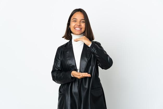 Молодая латинская женщина, изолированная на белом фоне, держит воображаемое пространство на ладони, чтобы вставить объявление