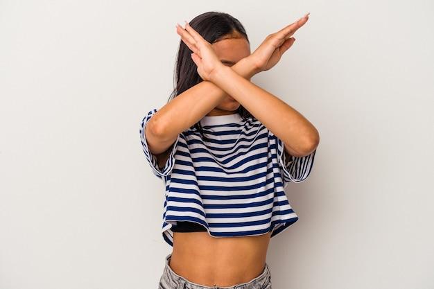 若いラテン女性は、2つの腕を交差させたまま、白い背景で隔離、概念を否定します。