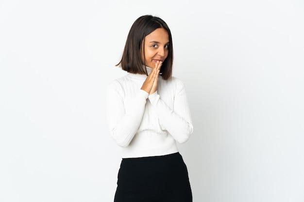 흰색 배경에 고립 된 젊은 라틴 여자 손바닥을 함께 유지합니다. 사람이 무언가를 요구한다