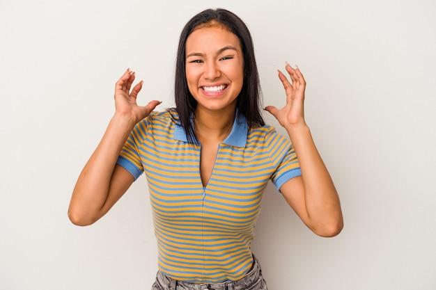 白い背景で隔離の若いラテン女性は胸に手を置いて大声で笑います。