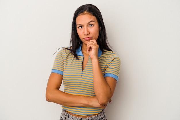 疑わしいと懐疑的な表情で横向きに白い背景で隔離の若いラテン女性。