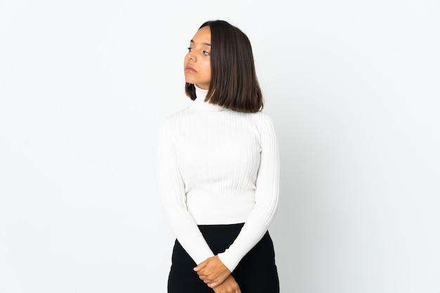Молодая латинская женщина изолирована на белом фоне, глядя в сторону