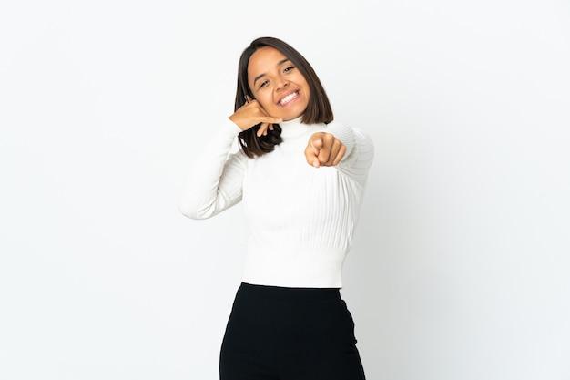 전화 제스처를 만들고 앞을 가리키는 흰색 배경에 고립 된 젊은 라틴 여자