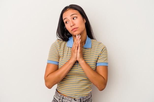 祈り、献身を示し、神のインスピレーションを探している宗教的な人を白い背景で隔離の若いラテン女性。
