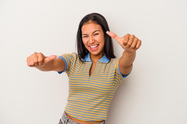 両方の親指を上げて、笑顔と自信を持って白い背景で隔離の若いラテン女性。 Premium写真
