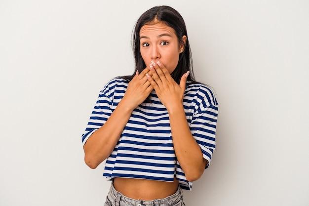 白い背景で隔離された若いラテン女性はショックを受け、手で口を覆い、何か新しいものを発見することを切望しています。
