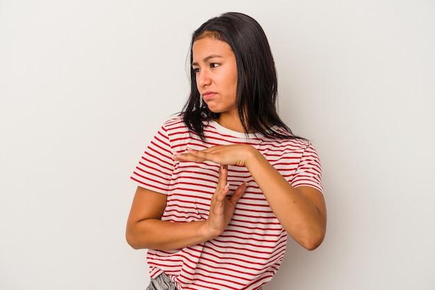 タイムアウトジェスチャーを示す白い背景で隔離の若いラテン女性。