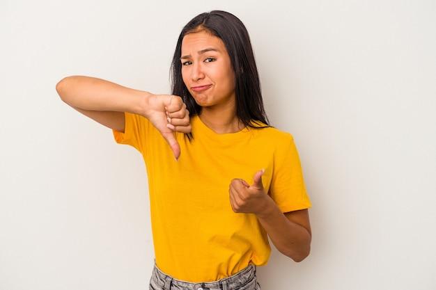 親指を上と親指を下に示す白い背景で隔離の若いラテン女性、難しい選択の概念