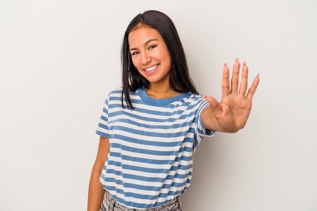 指で5番を示す陽気な笑顔の白い背景で隔離の若いラテン女性。