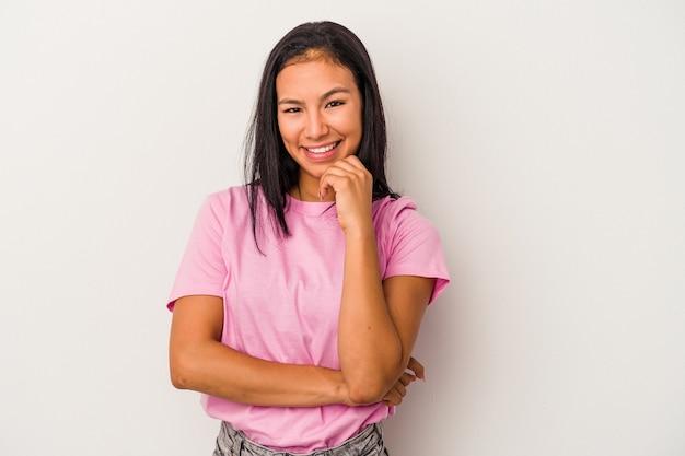 幸せと自信を持って笑顔、手で顎に触れて、白い背景で隔離の若いラテン女性。