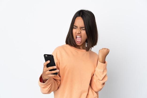 휴대 전화를 사용 하 고 승리 제스처를 하 고 흰색 배경에 고립 된 젊은 라틴 여자