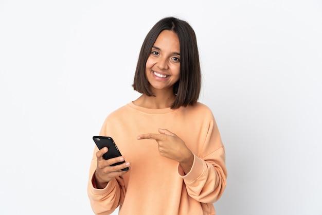 휴대 전화를 사용 하 고 그것을 가리키는 흰색 배경에 고립 된 젊은 라틴 여자