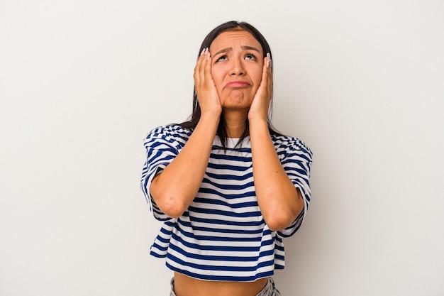 ひどく泣き叫びながら白い背景に孤立した若いラテン女性。
