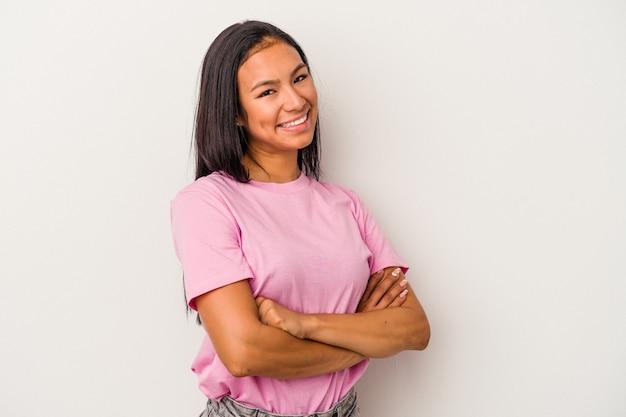自信を持って、決意を持って腕を組んで、白い背景に孤立した若いラテン女性。