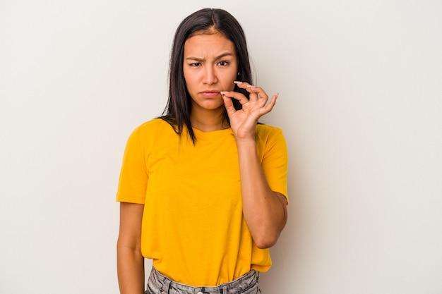 秘密を保持している唇に指で白い背景で隔離の若いラテン女性。