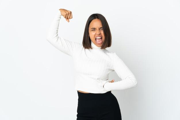 Молодая латинская женщина изолирована на белой стене празднует победу