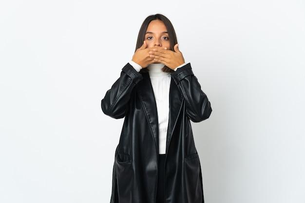 手で口を覆う白い壁に分離された若いラテン女性