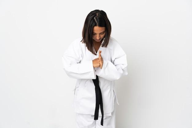 Молодая латинская женщина изолирована на белой стене, занимаясь карате и салютуя