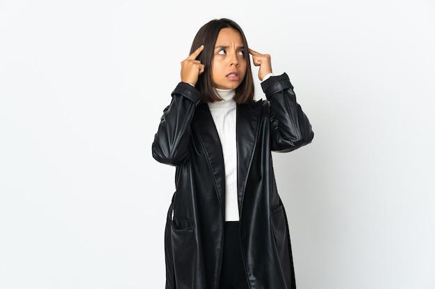 Молодая латинская женщина изолирована на белой стене с сомнениями и мышлением