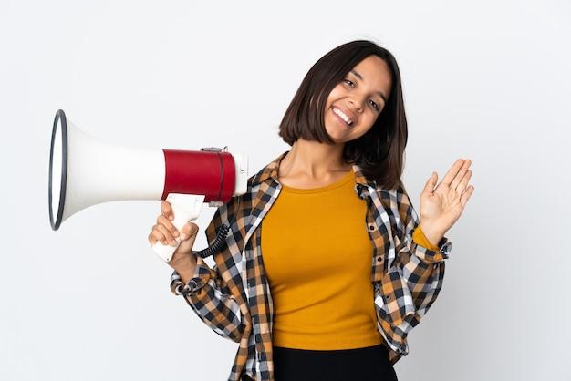 Молодая латинская женщина, изолированная на белой стене, держит мегафон и салютует рукой с счастливым выражением лица