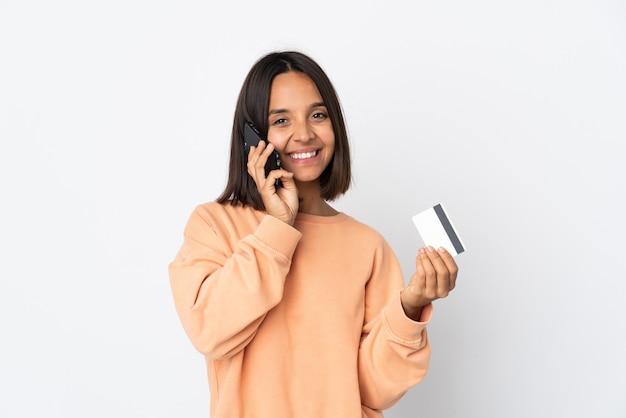 Молодая латинская женщина изолирована на белой стене, разговаривает по мобильному телефону и держит кредитную карту