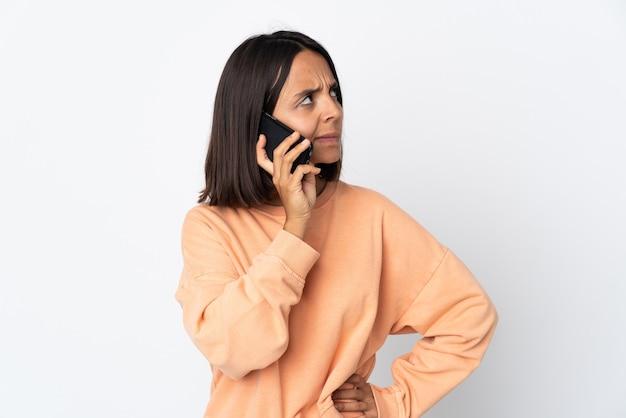 누군가와 휴대 전화로 대화를 유지하는 흰 벽에 고립 된 젊은 라틴 여자