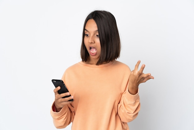 Молодая латинская женщина изолирована на белой стене, глядя в камеру, используя мобильный телефон с удивленным выражением лица