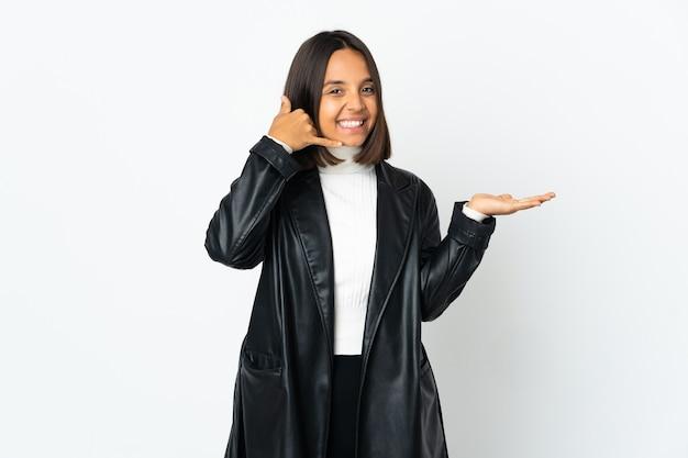 電話のジェスチャーをし、疑う白い壁に孤立した若いラテン女性