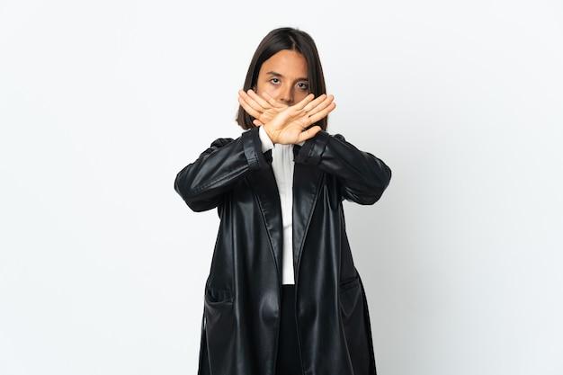 行為を停止するために彼女の手で停止ジェスチャーをしている白い壁に隔離された若いラテン女性