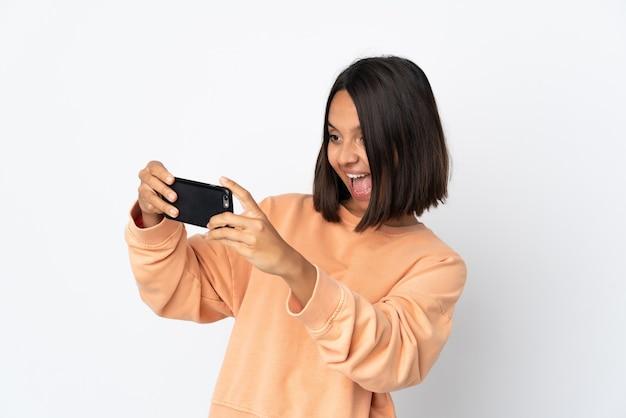 Молодая латинская женщина изолирована на белой стене, играя с мобильным телефоном