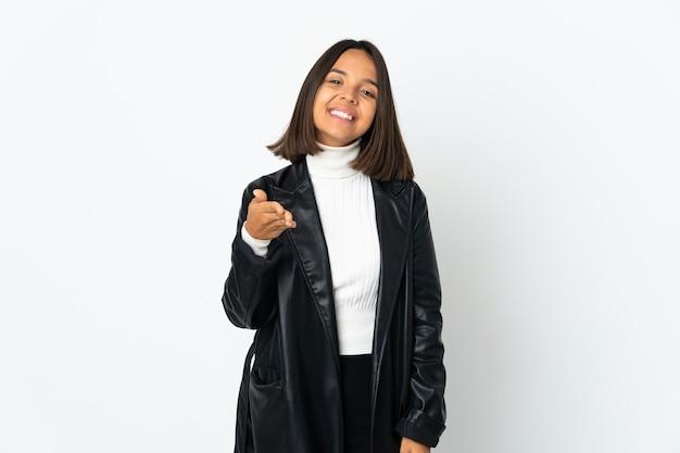 Молодая латинская женщина изолирована на белой стене, пожимая руку для заключения хорошей сделки