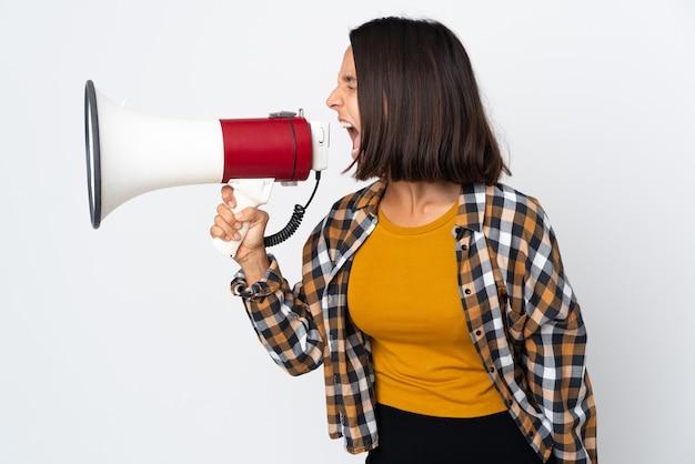 Молодая латинская женщина, изолированная на белой стене, кричит в мегафон, чтобы объявить что-то в боковом положении