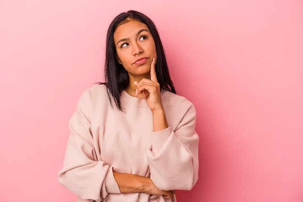 Young latin woman isolated on pink background  contemplating, planning a strategy, thinking about the way of a business.