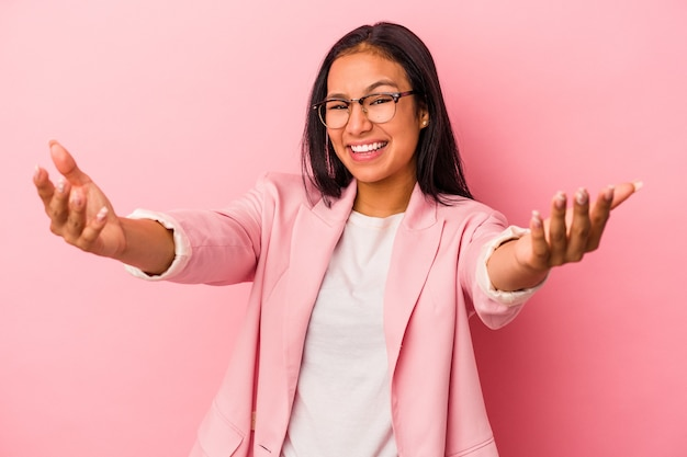 Young latin woman isolated on pink background  feels confident giving a hug to the camera. Premium Photo