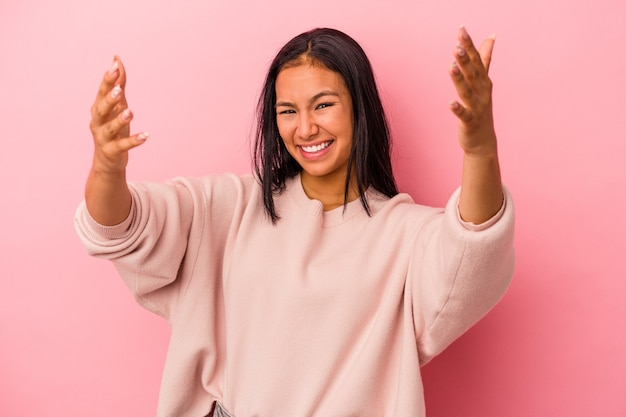 Young latin woman isolated on pink background  feels confident giving a hug to the camera.