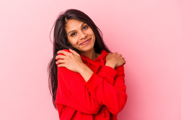 Young latin woman isolated on pink background hugs, smiling carefree and happy.