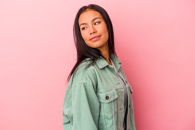 Young latin woman isolated on pink background  looks aside smiling, cheerful and pleasant.