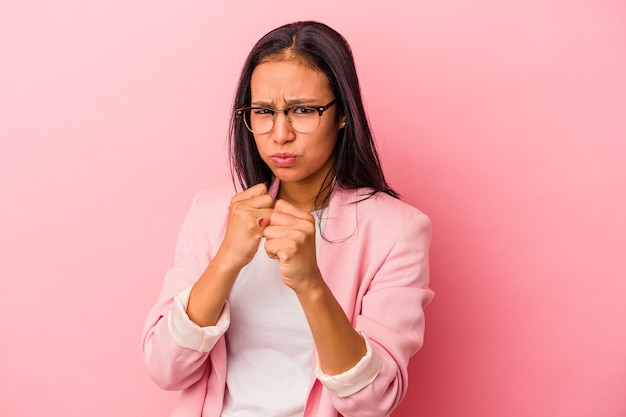 Young latin woman isolated on pink background  showing fist to camera, aggressive facial expression.