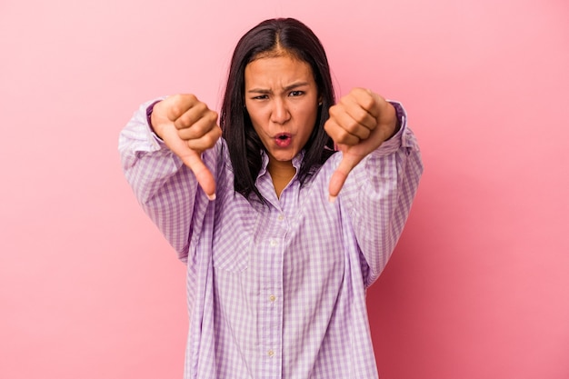 Young latin woman isolated on pink background  showing thumb down and expressing dislike.