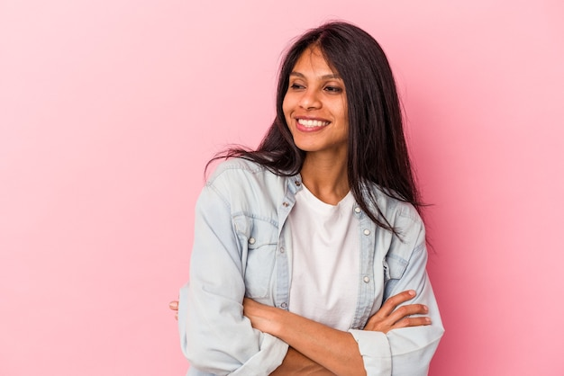 Young latin woman isolated on pink background smiling confident with crossed arms.