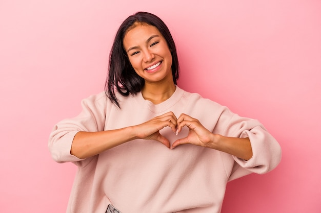 Young latin woman isolated on pink background  smiling and showing a heart shape with hands.