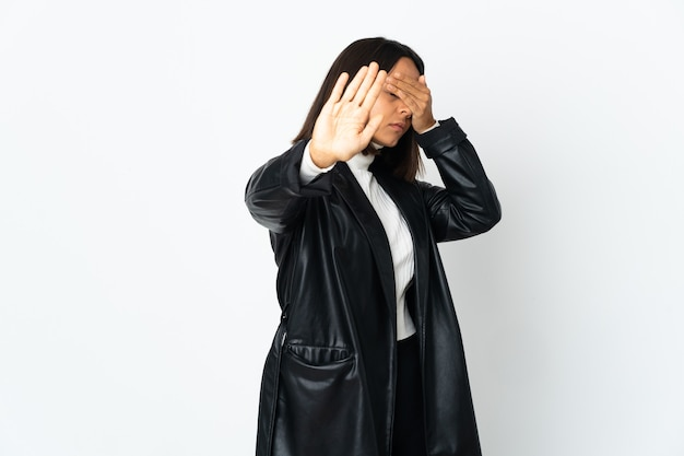 Young latin woman isolated on white background making stop gesture and covering face