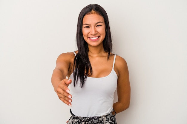 Young latin woman isolated on white background  stretching hand at camera in greeting gesture.